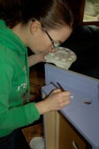 daughter Emelia painting beehives